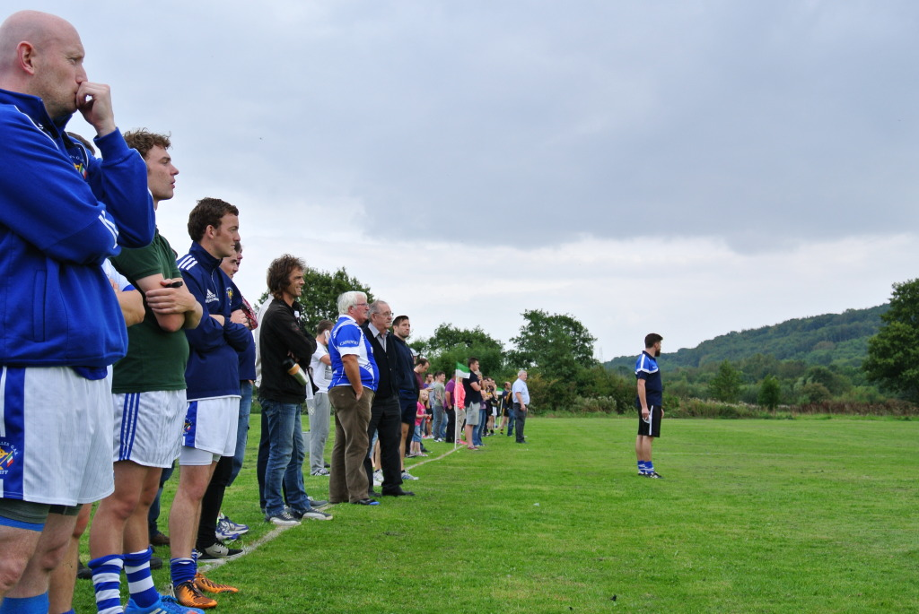 Spectators look on as Cardiff team Manager Eoin Butler surveys from the sideline